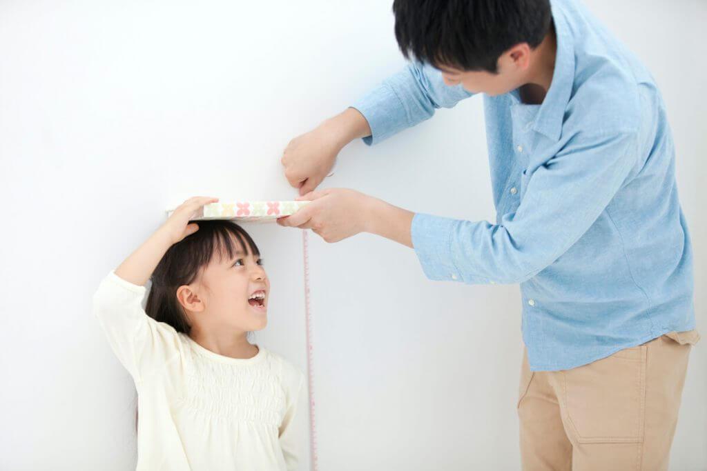 父親が女の子の身長を測っている様子