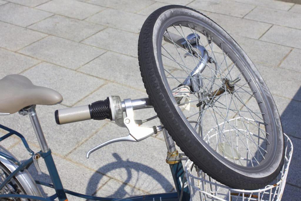 自転車のかごにタイヤを乗せている