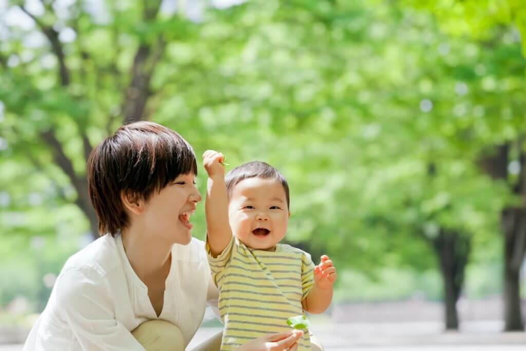公園で母親と遊ぶ小さな男の子