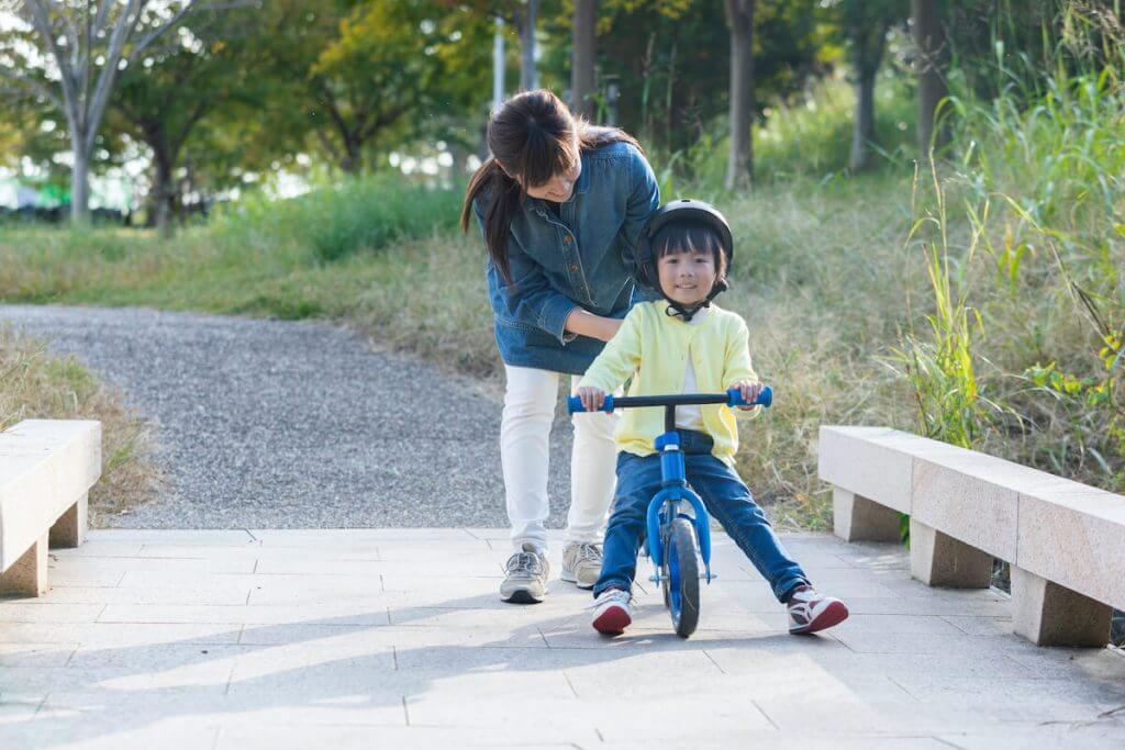 男の子がキックバイクに乗って自転車に乗る練習をしている様子