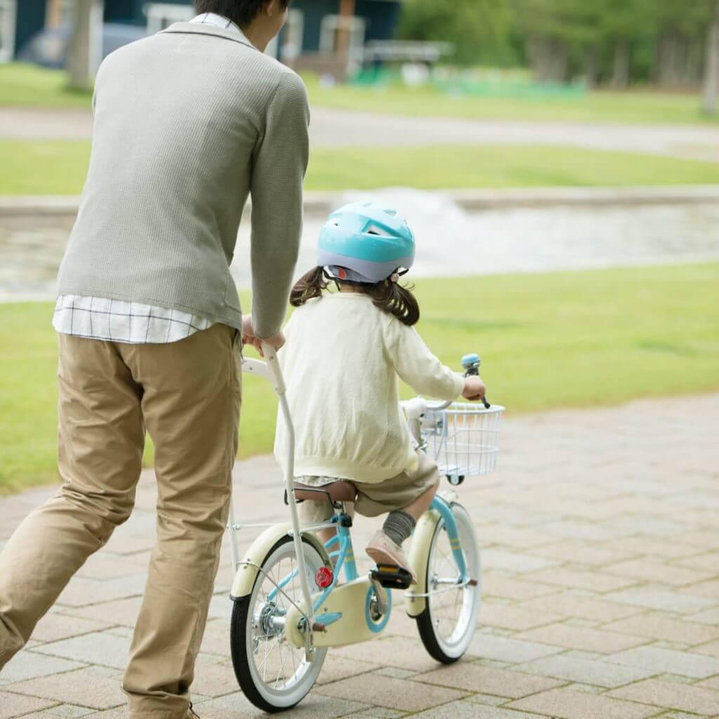 小さな女の子が自転車に乗る練習をしている様子