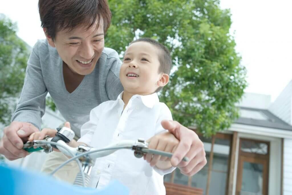 お父さんが子供の自転車の練習に付き合っている様子