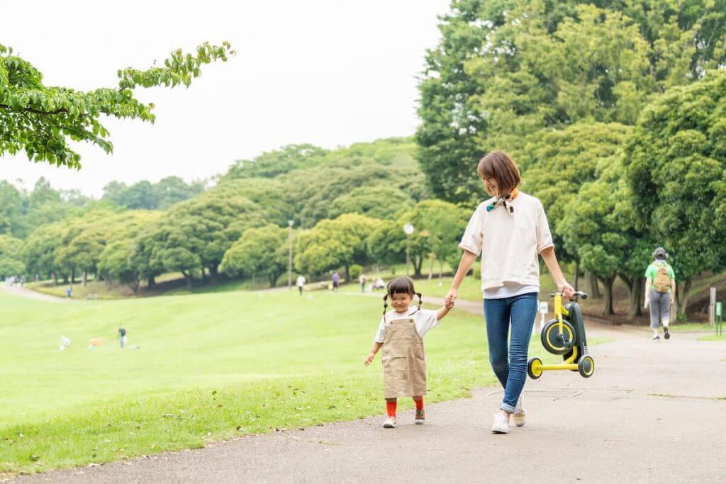 女の子が三輪車を持っているお母さんと歩いている様子
