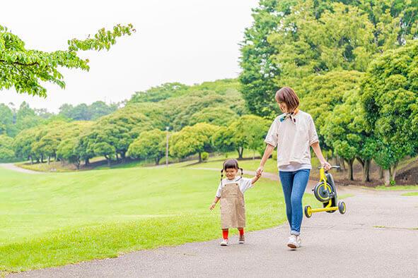 折りたたみ三輪車をもった親が子どもと歩いている様子
