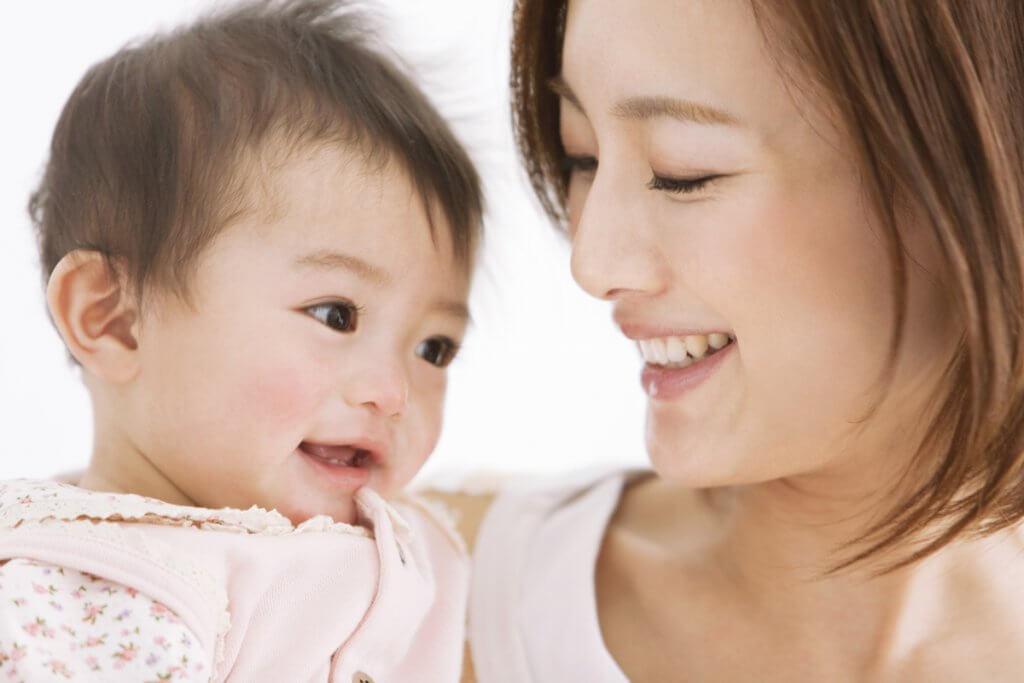 幼い子供を抱っこして笑う女性