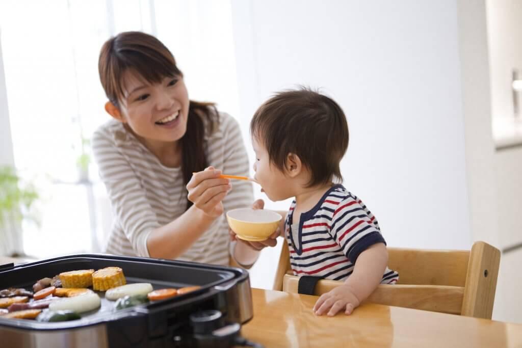 幼い子供にご飯を食べさせる母親
