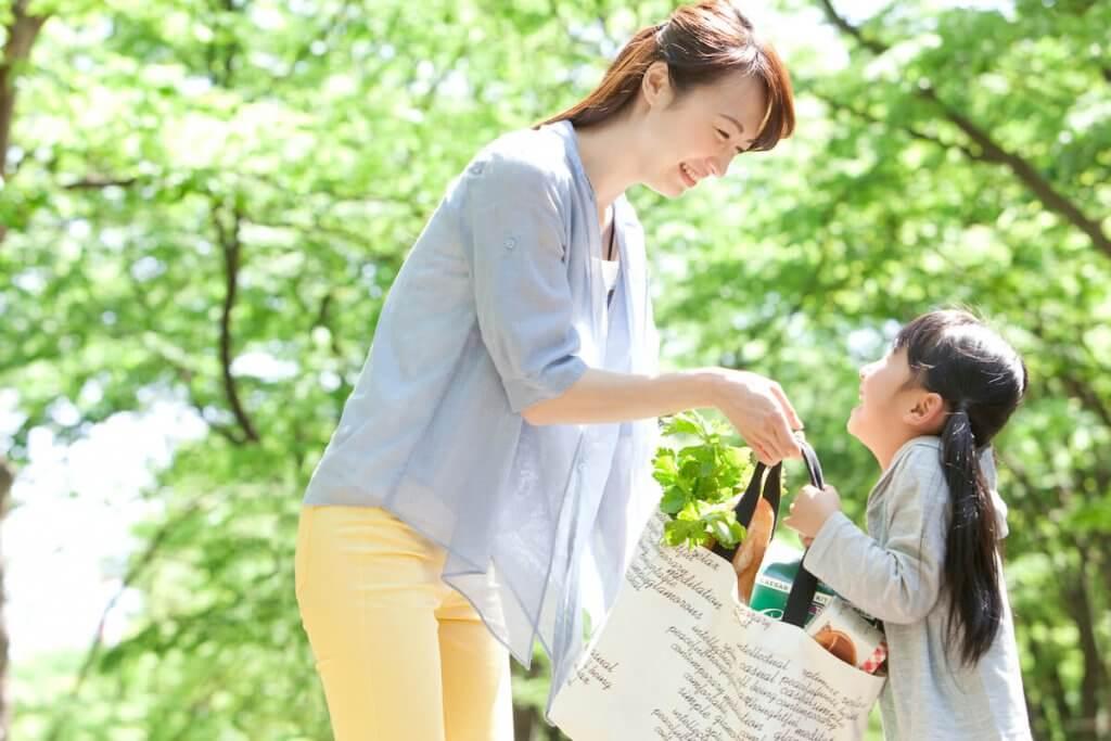 親が子供に荷物を渡している様子