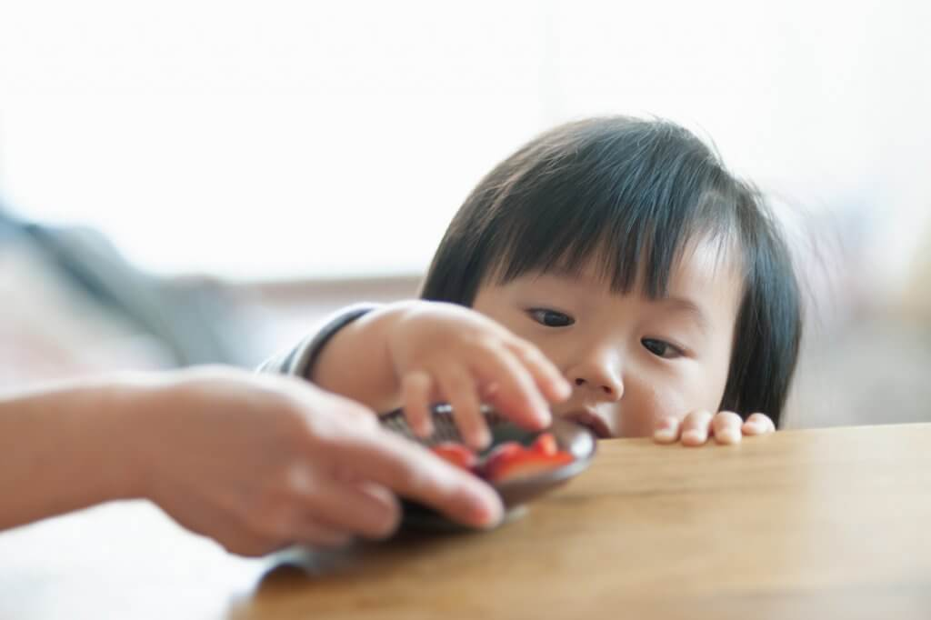 お皿に手を伸ばす子供