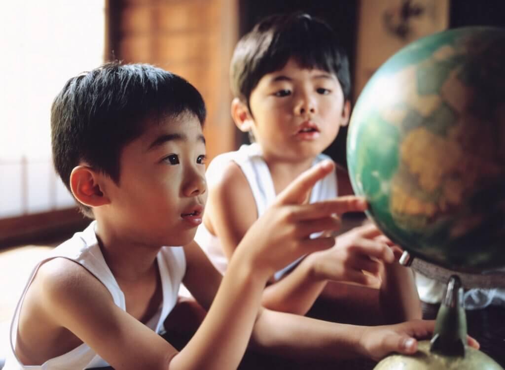 地球儀を見つめる2人の少年