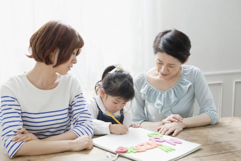 ノートに文字を書く子供と女性