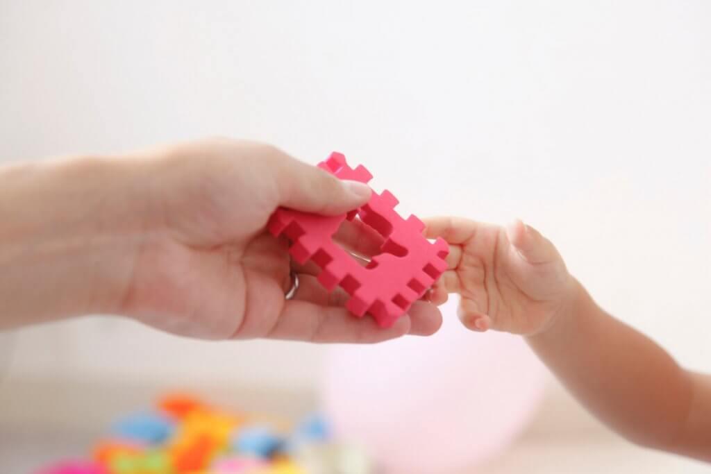 知育玩具を子供に差し出す手