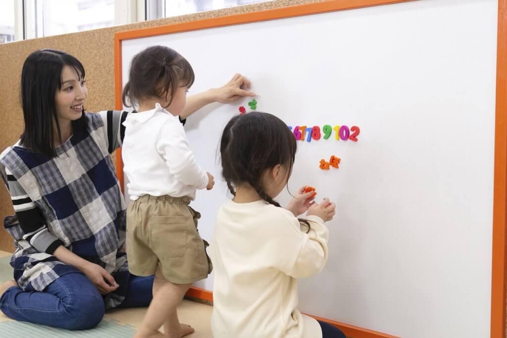 ホワイトボードに知育玩具を貼る子供たち