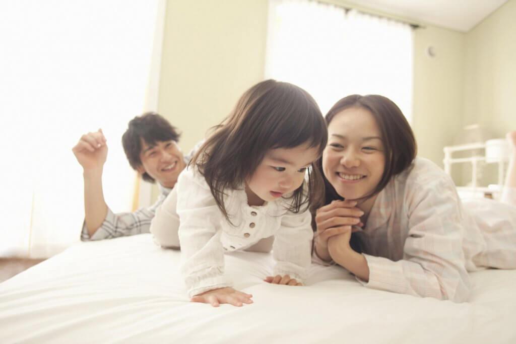 ベッドの上でハイハイをする娘と夫婦