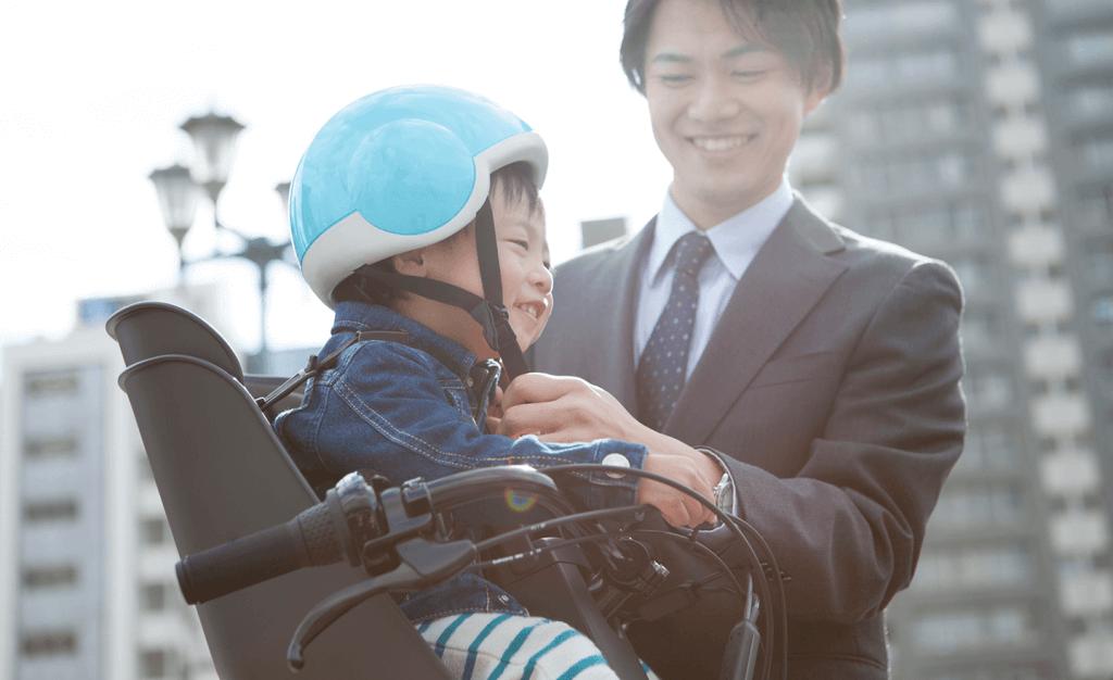 子どもにヘルメットをかぶせるパパ